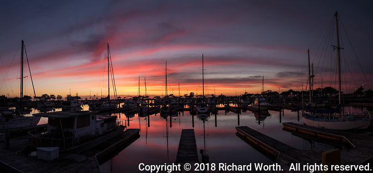 Ten images blended into a single panoramic of  sunset over the San Leandro Marina.  The high cost of dredging the channel from the marina into San Francisco Bay has doomed this marina to closure in the near future.