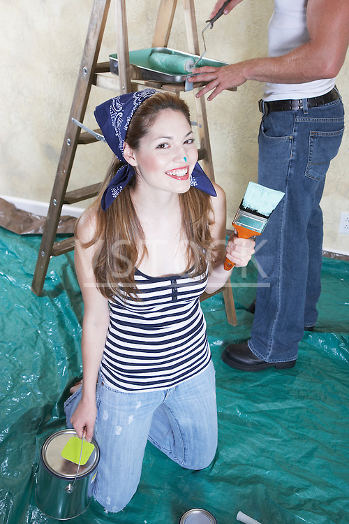 Portrait of smiling young woman holding paint can and paintbrush, man at ladder in background