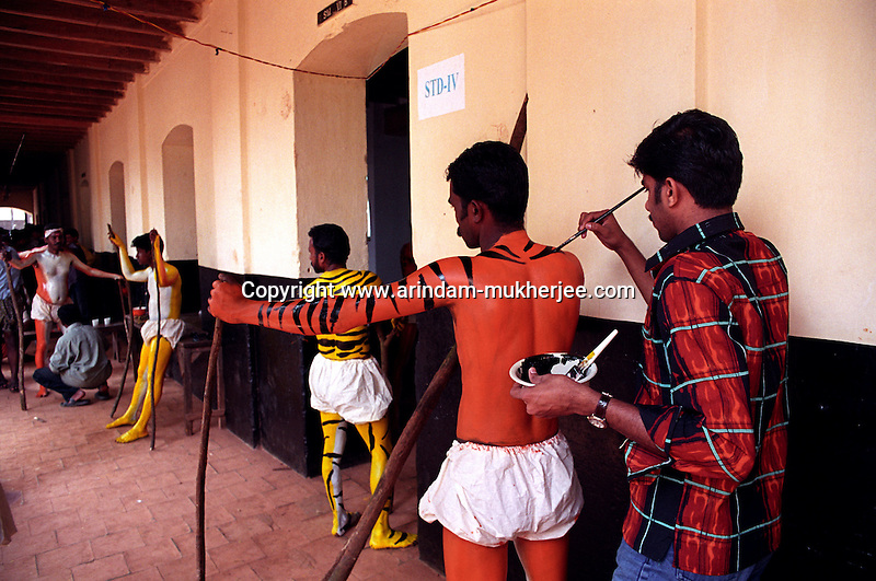 Local boys prepare themselves for Pulikali festival in a school building in Trichur, Kerala, India..Pulikali or Kaduvvakali is a two hundred year old folk dance form, practised mostly in Thrissur and Palghat districts of Kerala. It liberally makes use of forms and symbols of nature that finds expression in its bright, bold body painting and high-energy dance movements. The philosophy of Pulikali is that human and nature are integral parts of each other. So by fusing man and beast in its artistic language, it flamboyantly celebrates the connection. Arindam Mukherjee