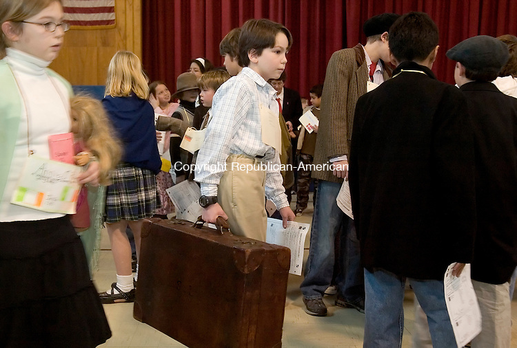 ROXBURY, CT-- 08 FEBRUARY 2008--020808JS01-Cory McGuinn, 10, who protrays and Irish immigrant, carries the suitcase his great-grandfather, Stephen Lucas, carried from Belfast, Northern Ireland to Ellis Island, during a day in the life of Ellis Island around the year 1900 Friday at Booth Free School in Roxbury. The students went through inspection stations and got a feel for what it was like for the millions of immigrants who came to this country through Ellis Island in New York. <br /> Jim Shannon/Republican-American