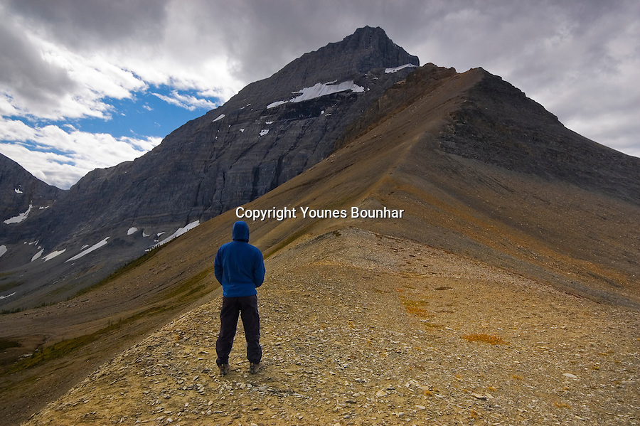 Man in blue jacket braving the cold and wind, standing at Numa pass looking at the towering rockwall above with menacing clouds overlooking the scene.