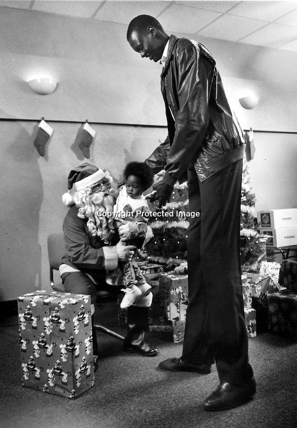 "Golden State Warrior center 7'7"" Manute Bol towers over Santa & child at Christmas party in Oakland,Ca<br />