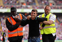 Pictured: A Crystal Palace supporter is escorted out by stadium stewards<br />