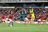 Kenny Dougall of Barnsley grabs the ball while challenged by Andre Ayew (22) and George Byers (28) of Swansea City during the Sky Bet Championship match between Barnsley and Swansea City at Oakwell Stadium, Barnsley, England, UK. Saturday 19 October 2019