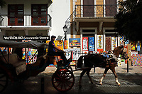 A man driving a horse and carriage and shops selling local handicrafts on the Calle Arzobispo Merino, in the Colonial Zone of Santo Domingo, Dominican Republic, in the Caribbean. Santo Domingo's Colonial Zone is listed as a UNESCO World Heritage Site. Picture by Manuel Cohen