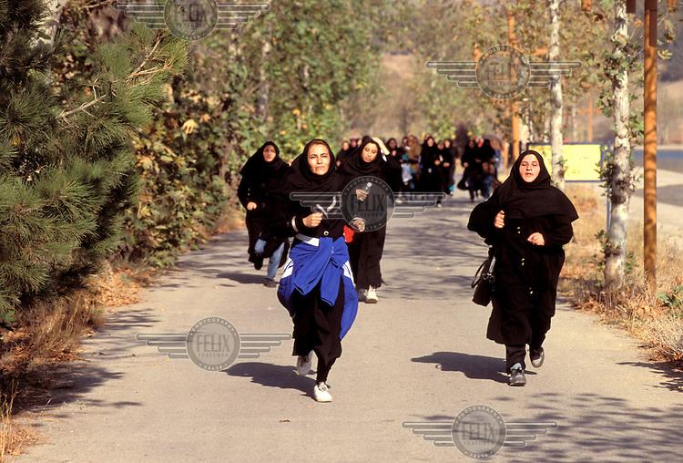 © Caroline Penn / Panos Pictures..Iranian women in sport..Tehran, Iran. October 1999...Wearing the full hijab, women running a mini-marathon during National Sports Week.