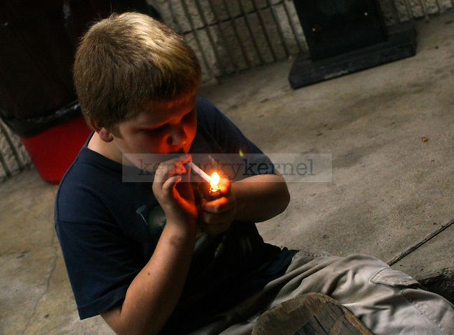 "William Slone, 11, smokes a cigarette outside of the Mi-Dee Mart in downtown Hindman, KY.  ""It's already lit so I might as well,"" Slone responds when his mother scolds him for smoking."