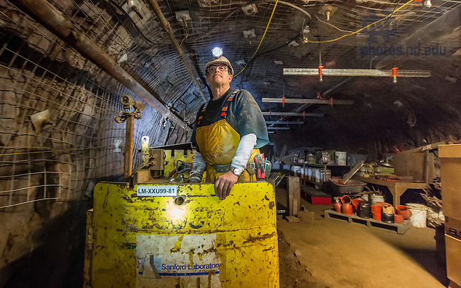 Jan 21, 2016; Infrastructure Technician and former gold miner Mike Oates, drives the train through a mine tunnel 4,850 below the surface in the Sanford Underground Research Facility in Lead South Dakota. The train used to move miners and ore, today it transports scientists and supplies. (Photo by Barbara Johnston/University of Notre Dame)