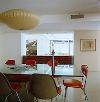 A George Nelson pendant light hangs above the glass-topped dining table