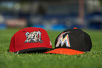 Batavia Muckdogs and Miami Marlins hats posed in the outfield grass after the teams first official practice on June 15, 2013 at Dwyer Stadium in Batavia, New York.  (Mike Janes/Four Seam Images)