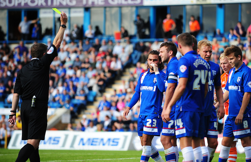 Gillingham's Doug Loft (2nd left, no. 7) is shown a yellow card by referee Garry Sutton for his protests at a Blackpool free kick<br /> <br /> Photographer Kevin Barnes/CameraSport<br /> <br /> Football - The Football League Sky Bet League One - Gillingham v Blackpool - Saturday 12th September 2015 - MEMS Priestfield Stadium - Gillingham<br /> <br /> &copy; CameraSport - 43 Linden Ave. Countesthorpe. Leicester. England. LE8 5PG - Tel: +44 (0) 116 277 4147 - admin@camerasport.com - www.camerasport.com