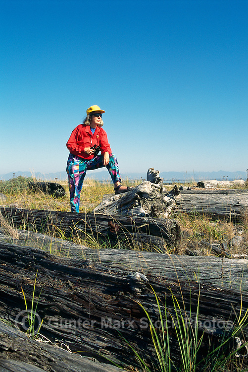 Woman standing on Log, and birdwatching / watching for Birds in Marsh, Boundary Bay Regional Park, Delta, BC, British Columbia, Canada (Model Released)