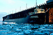 M/V William G Mather, part of the Cleveland-Cliffs Iron Company fleet, awaits a load of iron ore pellets at the LS&I ore dock in Marquette Michigan's upper harbor on Lake Superior. Circa Spring, 1970's