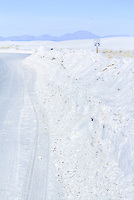 Sand covers the road and looks like snow drifts at White Sands National Monument in New Mexico.