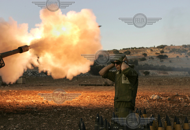 An Israeli soldier covers his ears while firing artillery from northern Israel into southern Lebanon during the war between Israel and Hezbollah.