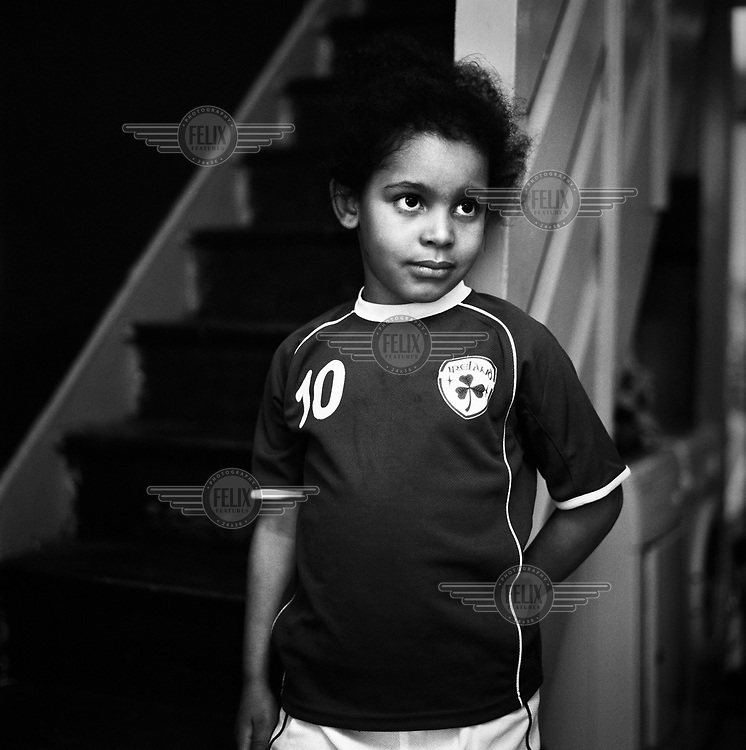 A young mixed-race girl, wearing a Republic of Ireland football shirt, stands in the hallway of a house on the Fettercairn Estate.