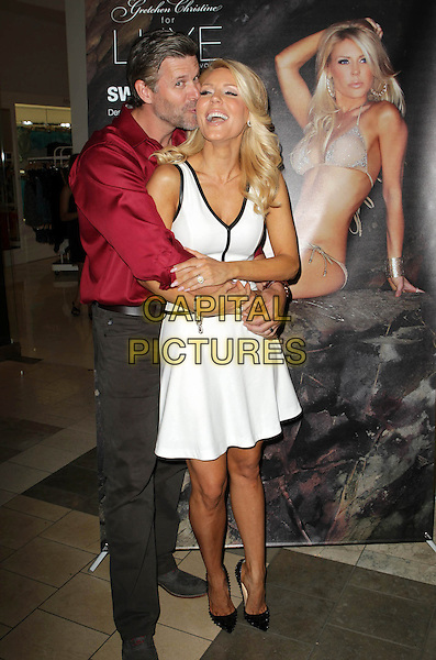 Slade Smiley, Gretchen Rossi<br /> Gretchen Christine for Luxe by Lisa Vogel Swimwear Held At SwimSpot Westfield, Woodland Hills, California, USA, 12th July 2013.<br /> full length red shirt arms around hug hugging  white sleeveless dress black trim shoes kissing kiss <br /> CAP/ADM/KB<br /> &copy;Kevan Brooks/AdMedia/Capital Pictures