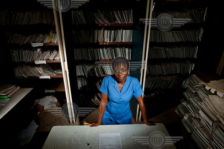 A member of staff sits at a desk surrounded by the records of the 43,170 patients treated to date. The records department has not been refurbished since it was constructed in 1975. Pantang Psychiatric Hospital