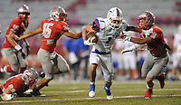 STAFF PHOTO ANDY SHUPE - Midland Christian's McLane Mannix (1) reaches to fend off Highland defensive back Austin Himschoot (2) after making a catch during the first half of play Monday, Sept. 1, 2014, at Razorback Stadium in Fayetteville.