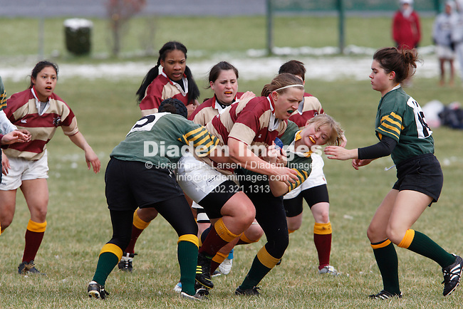 University of Pittsburgh players try to tackle a Norwich University ball carrier during a women's match at the annual Cherry Blossom Rugby Tournament at Rosecroft Raceway in Fort Washington, Maryland.
