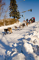 Misha Wiljes  and team  run past spectators and down the Cordova Street hill with an Iditarider in the<br /> basket and a handler during the Anchorage, Alaska ceremonial start on Saturday March 4th<br /> during the 2017 Iditarod race. Photo  @2017 by Kristie Lent/ SchultzPhoto.com