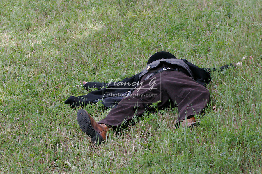 A cowboy laying in the grass after being shot dead at a 1800s western reenactment