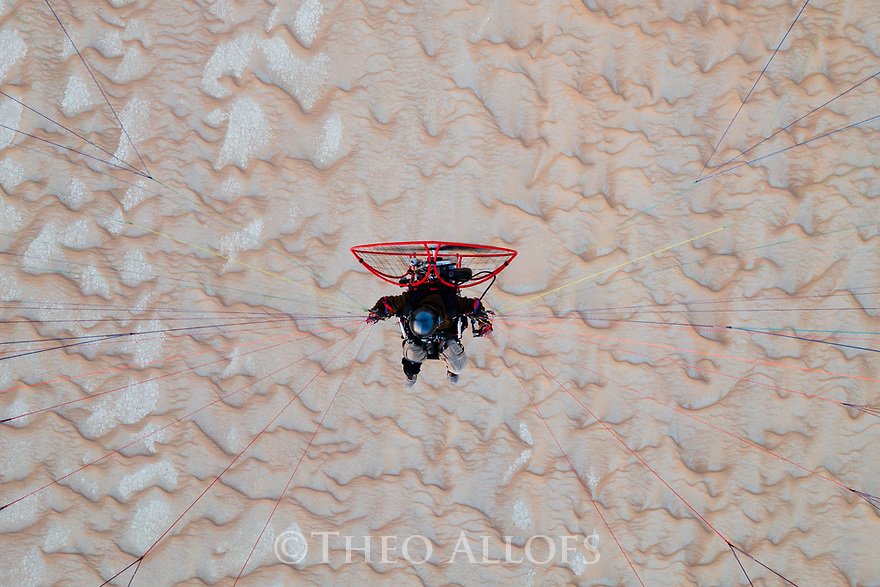 Chad (Tchad), North Africa, Sahara, photographer flying with powered paraglider above sand dunes; the camera is attached to the glider