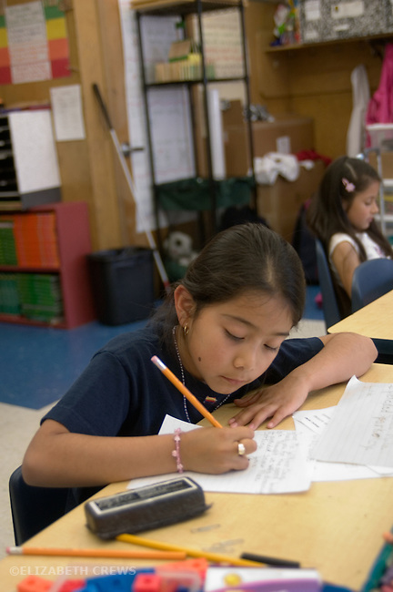Oakland CA Latina girl working on writing in 2nd grade class