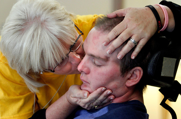 """I love you,"" Candi Diercks says to her son, Matt, 30,  while planting a kiss on his cheek while he rests before one of his therapy sessions at On With Life, a brain injury rehabilitation center in Ankeny.  Matt was injured in a motorcycle accident in July and has been rehabbing at On With Life since October.  Matt can't speak yet, but responds to his mother's kiss by opening and closing his jaw and an occasional moan.  Candi and her husband, Jeff, moved to Ankeny from Sabula to be near Matt while he recovers."