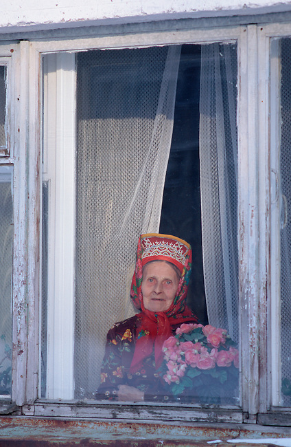 Maria Zakharova, an 82 year old Sami woman, at the window of her apartment in Lovozero. Murmansk, Kola Peninsula, NW Russia