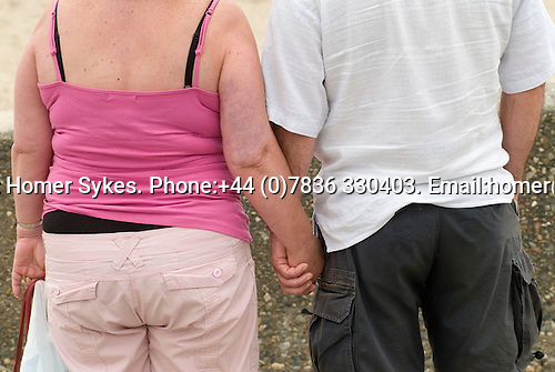 Ordinary overweight middle aged couple  holding hands on holiday Wales. UK 2008. Rear view.