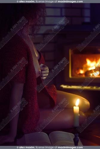 Artistic erotic photograph of a beautiful sexy half nude woman sitting by the fire with a book in a sweater over her naked body