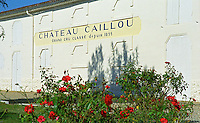 The winery Chateau Caillou in Sauternes, a sign painted on the wall and roses in the foreground.  Chateau Caillou, Grand Cru Classe, Barsac, Sauternes, Bordeaux, Aquitaine, Gironde, France, Europe