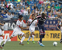 New England Revolution forward Saer Sene (39) dribbles and fends off D.C. United defender Daniel Woolard (21). In a Major League Soccer (MLS) match, the New England Revolution (blue) tied D.C. United (white), 0-0, at Gillette Stadium on June 8, 2013.