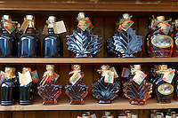 Bottles of Canadian maple syrup lined up on shelves at the Jean Talon Market, Montreal, Quebec, Canada