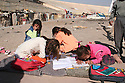 Iraq 2007 .Displaced Kurdish families in the stadium of Kirkuk, children reading their school books .Irak 2007 Familles  kurdes deplacees dans le stade de Kirkouk, enfants avec leurs livres d'ecole