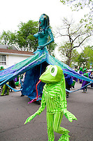 Frog walking beside goddess who rules over all who live in and use water. MayDay Parade and Festival. Minneapolis Minnesota USA
