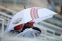 A fan uses an umbrella that looks like a baseball as a light rain falls during the South Atlantic League game between the Hickory Crawdads and the Kannapolis Intimidators at Kannapolis Intimidators Stadium on May 21, 2017 in Kannapolis, North Carolina.  The Intimidators defeated the Crawdads 9-8.  (Brian Westerholt/Four Seam Images)