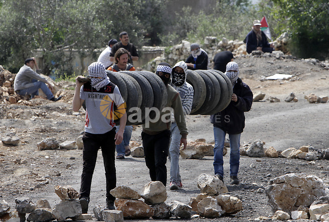 Palestinian protesters carry tyres during clashes with Israeli security forces following a rally in support of Palestinian President Mahmoud Abbas in the village of Kfar Qaddum, near Nablus, in the occupied West Bank, April 4, 2014. Israel has called off a planned release of Palestinian prisoners meant to advance the U.S.-sponsored peace process and called for a review of how the troubled negotiations can make progress, an official briefed on the talks said on Thursday. Photo by Nedal Eshtayah