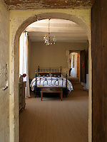 An antique bed is glimpsed through an archway in one of the bedrooms
