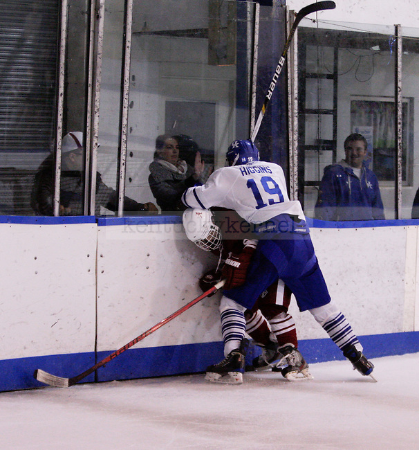 Freshman defender Dylan Higgins checks an Alabama player against the glass to steal the puck during the University of Kentucky's men's club hockey game at the Lexington Ice Center in  Lexington, Ky., on Friday, October. 19, 2012.