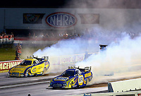Aug. 31, 2013; Clermont, IN, USA: NHRA funny car driver Ron Capps (near) does a burnout alongside Matt Hagan during qualifying for the US Nationals at Lucas Oil Raceway. Mandatory Credit: Mark J. Rebilas-