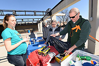 NWA Democrat-Gazette/FLIP PUTTHOFF<br /> SPRING CREEK CLEANING<br /> Rachel Kraus (left) with Washington County Environmental Affairs helps Monroe Corwin (right) pick up supplies Wednesday March 14 2018 for a  cleanup of Spring Creek in the area of downtown Springdale. Dozens of volunteers waded the creek and shoreline to spruce up the creek. Washington County Environmental Affairs, Downtown Springdale Alliance and University of Arkansas Extension Service teamed up to host the event. Volunteers included community members, scouts and Tyson Foods employees who were allowed to leave work early to help.