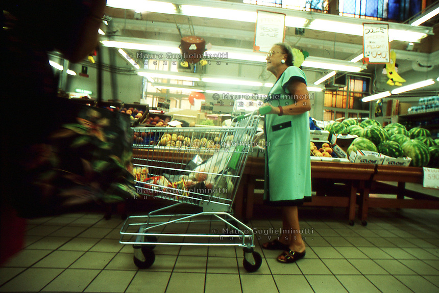 signora con carrello all'interno di un supermercato nel settore ortofrutta<br />