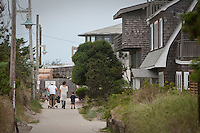 People walk in an Ocean Beach street on Fire Island in New York state, Wednesday August 3, 2011. The incorporated villages of Ocean Beach and Saltaire within Fire Island National Seashore are car-free during the summer tourist season and permit only pedestrian and bicycle traffic.