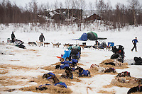Allen Moore leaves on the Iditarod River with delapidated buildings of the ghost town of Iditarod in the background on Friday March 8, 2013...Iditarod Sled Dog Race 2013..Photo by Jeff Schultz copyright 2013 DO NOT REPRODUCE WITHOUT PERMISSION
