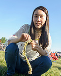 A near record crowd hot air balloon fans filled the hillsides at the National Balloon Classic launch field July 29 for opening ceremonies, balloon launches and music. Ibuki Miyagawa of Kofu, Japan found clover blooms in the seating area of the launch field to make a necklace made of the blooms. She is among a groups of exchange students attending a Lincoln High program through Central Academy. They are hosted by Iowa Sister Schools.