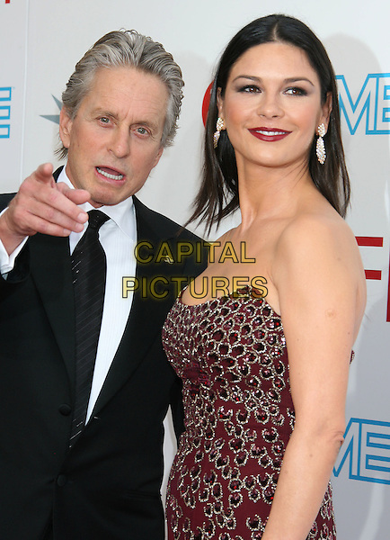 MICHAEL DOUGLAS & CATHERINE ZETA-JONES.37th AFI Life Achievement Awards, Sony Pictures Studios,  Culver City, California, USA..June 11th, 2009.half length black suit red maroon burgundy dress slit split jewel encrusted embellished strapless married husband wife lipstick dangling earrings hand mouth open finger pointing .CAP/ADM/MJ.©Michael Jade/AdMedia/Capital Pictures.