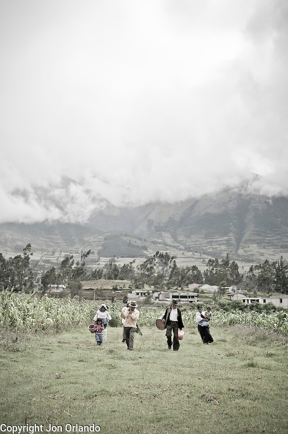 Members of The Pakarinka Sisari Ancestral Wisdom Center near Otavalo, Ecuador,  head home after harvesting fava beans.