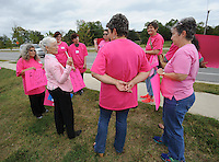 NWA Democrat-Gazette/ANDY SHUPE<br /> Gladys Tiffany (center), director of the OMNI Center for Peace, Justice &amp; Ecology in Fayetteville, speaks with residents Wednesday, Sept. 30, 2015, during a rally in support of Planned Parenthood along Crossover Road in Fayetteville. The rally was organized by members of the Omni Center for Peace, Justice and Ecology's EcoFeminist Study and Action Group as a part of a national rally in support of Planned Parenthood's Pink Out day, which was Tuesday.